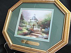 Thomas Kinkade Picture and Frame--Has gold wood frame with glass, green matt and garden scene with gazebo--Has gold strip that says Thomas Kinkade