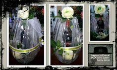 Butelka wina w szklanym flakonie ozdobiona sztucznymi kwiatami.