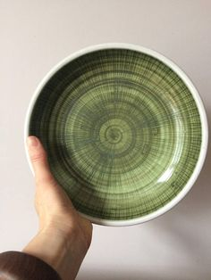 Vintage early RYE Pottery Green Mid Century Scrafitto Bowl from the 1950s. Energetic hand painted swirls of dark green, leaf green and charcoal grey bring this simple form to life. The Rye mark is clearly stamped on the base. This studio pottery dish will display well in any mid century or modern interior.  Measurements: Diameter 21.5 cm, H 5cm  Condition: This example is in very good condition. Please study the photographs closely as they are part of the description.  Note: We try to be as…