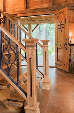 "Open stairs, accented with wrought-iron, lead up to the barn's living spaces. The main level offers plenty of space, as well as storage area for Tom's ""toys."""