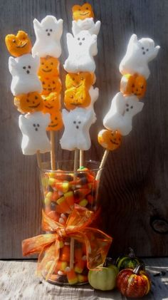 simple diy edible halloween centerpiece - just tie a festive ribbon on a glass vase and fill with candy corn and stick skewers inside with halloween pumpkin and ghost peeps on them.