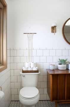 Modern Vintage Bathroom including white tile and black grout throughout. Loving the antique brass pendant lighting and vintage console turned custom vanity.