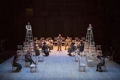 A platform with chairs, two ladders topped by George and Emily, their siblings seated in chairs below, his father, too, and toward the back ...