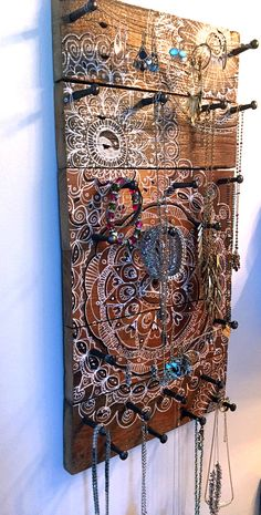 This is a large jewelry holder that I made out of wood from an old fence that we took down in the backyard. The wood is very rustic and I have painted it with my mandala doodles. #jewelry holder #jewelry organizer #reclaimed wood #wood projects #mandala art #boho art