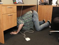 Area Man Crawling On Ground Like Pig To Plug Macbook Power Cord Behind Desk
