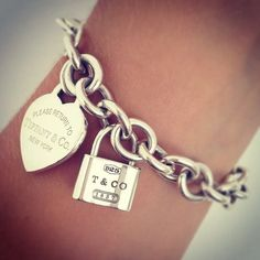This Bracelet tiffany and co is so cute love the shinning silver and the heart locket  Charm Bracelet :)