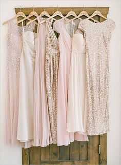 Pink, rose gold and gold bridesmaids dresses hung up on display