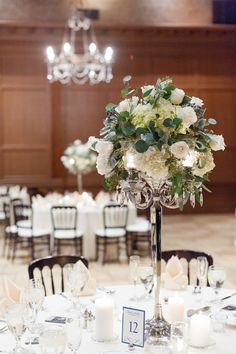 A candelabra and a white rose, white hydrangea, and brunia bell flower arrangement for this centerpiece   Leslie Ann Photography   villasiena.cc