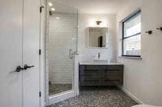 """""""After"""" photos of 10th flip - It's Great to Be Home.  Gray and white modern bathroom with gray penny tile floor, floating Ikea Godmorgon vanity, frameless glass shower, white subway tile with gray grout, black hardware"""