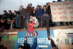 People from East Germany greet West German residents at the Berlin Wall in front of the Brandenburg Gate.