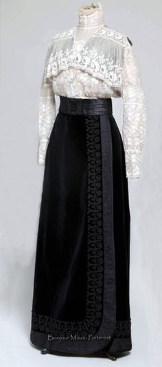 S: http://athena.muo.hr/?object=detail&id=26691 IOC: Blouse & skirt, Croatia, ca. 1908–09. Blouse is 2 types of lace on tulle. High neckline shown, to create a turtle neck. The skirt is black velvet, with detail along the left side of the hip.