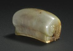 A CELADON AND RUSSET JADE HAIR ORNAMENT MING DYNASTY, carved with a curved top and coiled at the ends to resemble a scroll, the interior hollow to fit over a topknot, with holes in the ends to secure a hairpin, the stone with a slight yellow tinge, russet mottling and opaque inclusions, box.