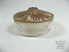 "Clematite, Coty Creme Pot  Type:Creme pot    Material(s):Glass    Designer/Maker:Lalique    Markings:Molded ""Coty"" and ""Paris"" on lid edge, and ""Coty"" and ""France"" on the inside of base.    Label:none    Origin:France    Date or Era:c. 1911    Dimensions:2.6 in/6.6 cm. diameter    Additional Information:  Clear and frosted glass with high relief molded flower lid with a brown patina; clear base with four scallops. This piece also known with blue patina."