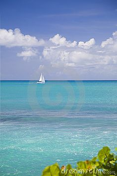 A sailboat on the horizon from the shores of the Caribbean island of Antigua.