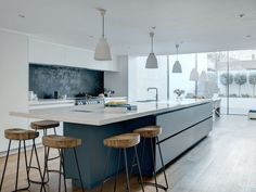 Island with 6 seats, matt walnut lacquer on shelves in pantry, caesarstone and blue feature island
