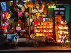 Two women in Hoi An, Vietnam, pass the time at a lantern shop in this National Geographic Photo of the Day.