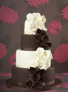 I am salivating even looking at these 4-tiers of decadance! Alternating layers covered in chocolate & what } will say is whit chocolate, each layer with a small ribbon trim at the bottom of the tier. Then cascading down the cake are matching hand-carved roses. Absolutely rich & elegant...now tell me the filing is Godiva liqour & I'm there.