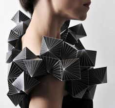 The geometric shapes and forms are very bold. The whit lines emphasis that sharp corners and bold edges. This makes her neck seem bolder and more pronounced than before.