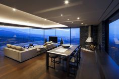 Delightful Open Dining Area With Modern Table And Chairs Along With Lower Wooden Cupboard And Fireplace Decorated By Glass Wall And Recessed Ceiling Lamps Minimalist House on the Slope Demonstrates Breathtaking Views Home design