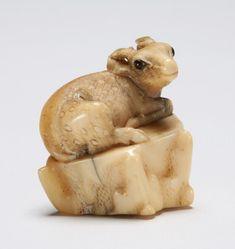 Fossil ivory netsuke showing a deer resting on a rock