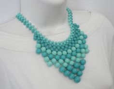 Maxi colar confeccionado com bolas em resina, nas cores turquesa e verde água. Acabamentos em metal niquelado. <br>Comprimento: 43 cm + 5 cm de corrente extensora <br>Altura meio do colar: 10cm