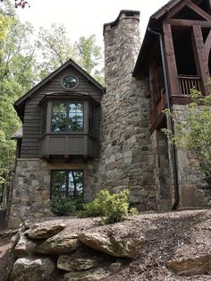 Beautiful home on Lake Keowee with English Arts and Crafts inspired details. The exterior combines stone and wavy edge siding with a cedar shake roof. Inside, heavy timber construction is accented by reclaimed heart pine floors and shiplap walls. The three-sided stone tower fireplace faces the great room, covered porch and master bedroom.