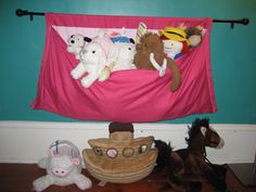 """Stuffed animal storage for easy kid access. A curtain rod supports a curtain panel, sewn into a """"pocket"""" by folding it in half and stitching the sides."""