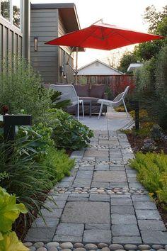 une allée de jardin en pavés gris et pierres décoratives
