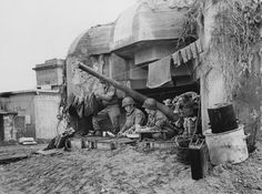 GIs are doing laundry using a German pillbox as a temporary shelter. The 75mm gun serves a novel purpose, i.e.helping to tie the string for hanging the laundry, France, 1944.