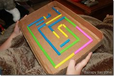 Homemade cardboard marble maze. Good for wrist mobility and problem solving!