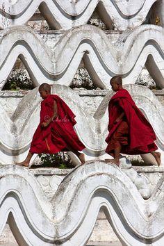 Myanmar/Burma, near Mandalay.Two young novice Buddhist monks walking on the Hsinbyume Paya, a stupa built in 1816. (Cecil image)