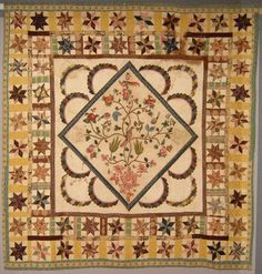 """Tree of Life quilt, made by Mary Minor Simms Lester sometime between 1800 and 1849.  It appears that this could be Broderie Perse in the center, instead of a printed panel.  It is surrounded by hand applique semi-circles cut from two different fabrics.  It is then bordered by LeMoyne stars, sashing, and a striped border print. It is a treasure trove of fabrics! It measures 86"""" x 90""""."""