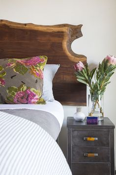 Such a nice vignette. I love the cabbage rose pillow against the live edge headboard with the brushed steel nightstand.