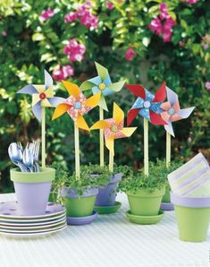Pretty pinwheels  Have fun with your centerpiece! Plant low-growing or trailing flowers or greenery in terra cotta pots painted in your favorite color, then insert a big store-bought or homemade pinwheel into each pot! Use empty painted pots to hold silverware and napkins