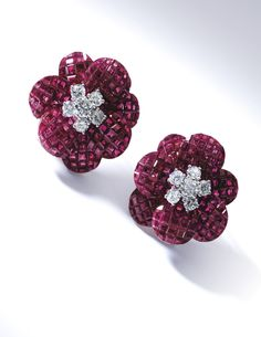 PAIR OF RUBY AND DIAMOND CLIP-BROOCHES, VAN CLEEF & ARPELS Each designed as a poppy, the petals composed of calibré-cut rubies en serti myst...