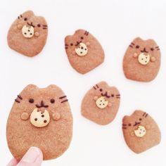 Pusheen cookies holding chocolate chip cookies.