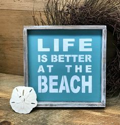 """This framed wooden beach sign reads """"Life is Better at the Beach"""". It measures approx 10"""" W x 10"""" H It is painted a Seaside Cottage color and has a router spot in back for hanging. All of our signs ar"""