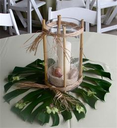 Candle, sand & shells wrapped in bamboo shoots w/raffia over a huge Monstera & green dendros