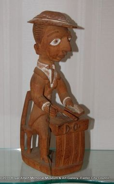 figure of a District Officer - This carving is of a colonial officer. He is shown seated and wearing formal clothing appropriate to the role. His hat and glasses are detachable. The figure combines a traditional Yoruba carving technique with modern imagery. This carving is probably satirical. - Royal Albert Memorial Museum & Art Gallery, Exeter