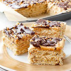 Ciasto Snickers bez pieczenia na herbatnikach, z kajmakowo-orzechową masą budyniową, orzeszkami ziemnymi i polewą czekoladową. Pyszne, proste i szybkie ciasto bez pieczenia.