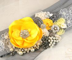 Sash- Bridal Sash in Yellow, Grey and Silver with Satin Flowers, Lace, Jewels, Vintage Brooches, Pearls and Crystals. $195.00, via Etsy.