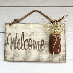 As friends, family, and strangers approach your home you want them to be imbued with warmth, excitement, and most importantly acceptance. This rustic wooden sign captures those positive emotions by combining the country chic styles of distressed wood with a Mason jar vase. This wooden