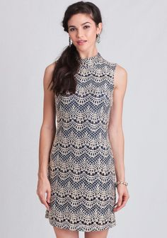 Refined and elegant, this navy sheath dress is adorned with a lace overlay with cream-hued embroidery in a scalloped motif. Designed with a mock turtleneck and a hidden back zipper closure, this ...