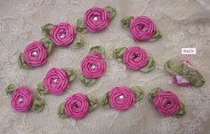 Thank you for stopping by my store today.  Measurement ~ 1 & 1/4 inches across which includes the green ribbon leaf. The spider rose flower itself measures 5/8 inches across. These flowers are handmade so the sizes may vary slightly.  Up for your consideration is one 12 pc set of FUCHSIA PINK floral HANDMADE ribbon flower appliques. These delicate pieces are HAND STITCHED with ribbons to form spider roses w 2 green leaves. The centers of the spider rose flowers are embellished with acrylic…