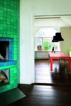 Den store grønne pejs i køkkenet er beklædt med lavasten fra Made a Mano. Farverne er nøje udvalgt for at skabe e...