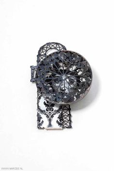 Vera Siemund - brooch, 2012, enamelled steel, silver embossed, sawn, enamelled (printed portrait), mounted - 70 x 100 x 35 mm - hemisphere covered with a rose window, inside a portrait, mounted on a floor plan