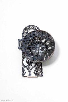 Vera Siemund - brooch, 2012, enamelled steel, silver embossed, sawn, enamelled (printed portrait), mounted - 70 x 100 x 35 mm - hemisphere covered with a rose window, inside a portrait, mounted on a floor plan