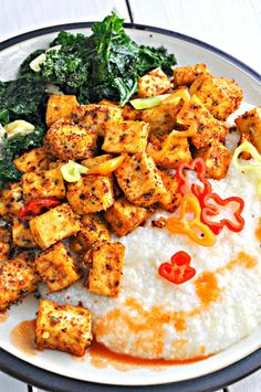 Crispy Cajun spiced tofu served with creamy grits and super garlicky greens. So perfectly spicy and totally delicious! The best Southern flavors made vegan!