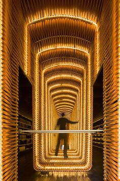 Matadero - pt 3    The film library is outfitted with black washed wood planks on the floors, walls, and ceilings, and has an elongated stair case that shoots through the center of the floors. The vertical railings of the stairs are horizontally intertwined with clear plastic tubing with warm lighting weaved between; an effect which causes a luminous glow, lighting up the entire library.