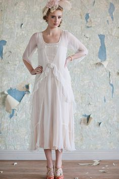 A peach crepe slip sits underneath an ethereal overlay of sheer ivory crinkle chiffon. A tiered ruffled hem, three-quarter length angel sleeves, and a vintage lace up detail add the perfect romantic accents.